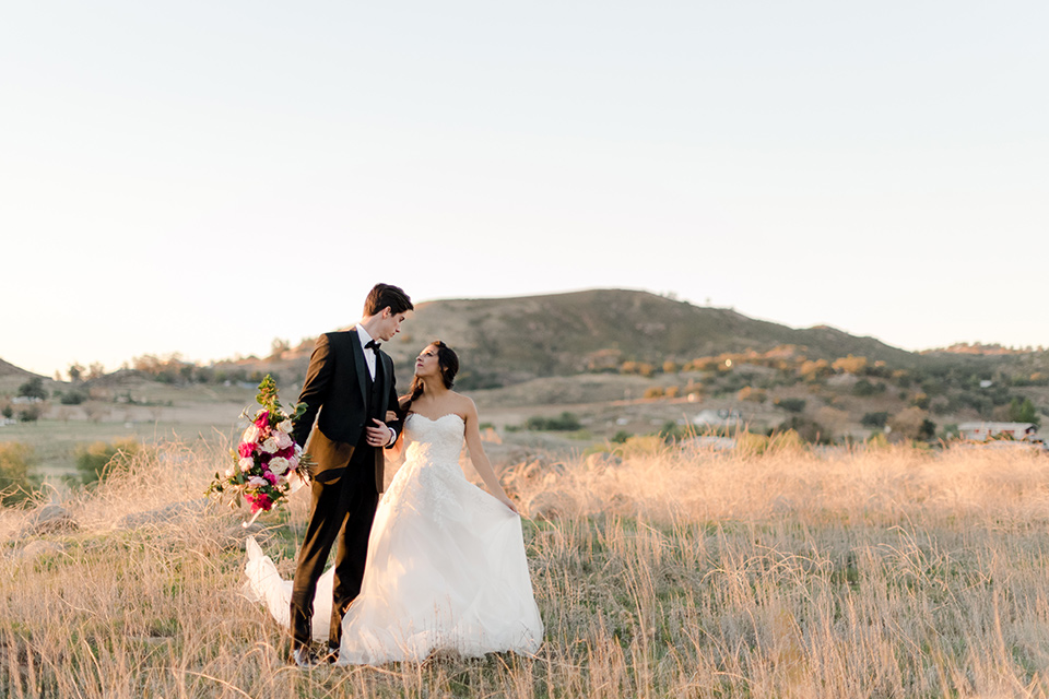 milagro-winery-bride-and-groom-walking-though-meadow-bride-in-a-tulle-ball-gown-groom-in-a-black-shawl-lapel-tuxedo