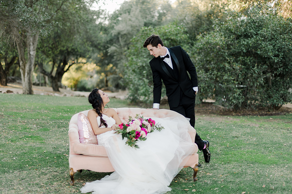 milagro-winery-bride-on-couch-groom-standing-bride-in-a-tulle-ball-gown-groom-in-a-black-shawl-lapel-tuxedo