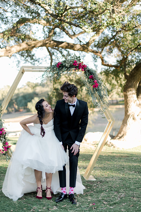 milagro-winery-couple-showing-socks-bride-in-a-tulle-ball-gown-groom-in-a-traditional-shawl-lapel-tuxedo-with-black-bow-tie