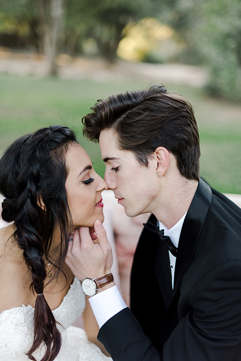 milagro-winery-groom-about-to-kiss-bride-close-bride-in-a-tulle-ball-gown-groom-in-a-traditional-shawl-lapel-tuxedo-with-black-bow-tie