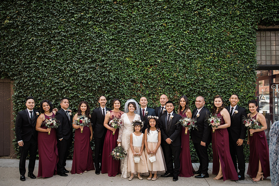 villa-del-sol-wedding-bridal-party-bridesmaids-in-burgundy-dresses-groomsmen-in-black-shawl-lapel-tuxedos-bride-in-a-spanish-inspired-lace-gown-with-a-deep-v-and-long-sleeves-groom-in-a-navy-shawl-lapel-tuxedo-with-a-burgundy-tie