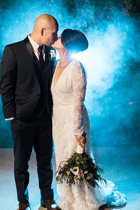 villa-del-sol-wedding-bride-and-groom-with-fog-behind-them-bride-in-a-spanish-inspired-lace-gown-with-sleeves-groom-in-a-navy-shawl-lapel-tuxedo-with-a-burgundy-tie