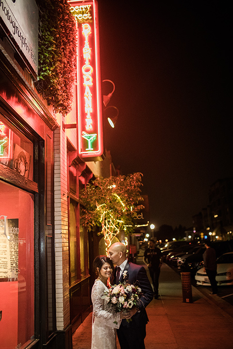 villa-del-sol-wedding-bride-and-groom-with-neon-signs-bride-in-a-lace-gown-with-long-sleeves-groom-in-a-navy-shawl-lapel-tuxedo-with-a-burgundy-tie