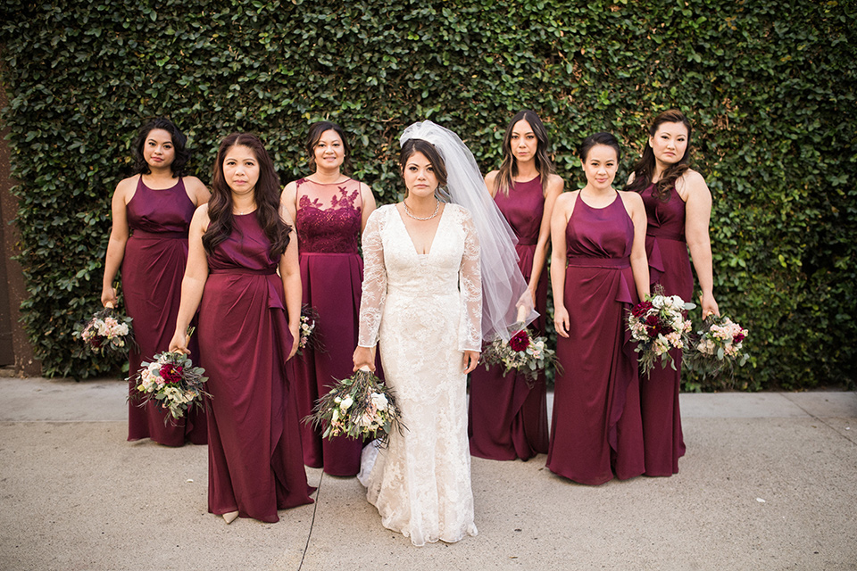villa-del-sol-wedding-bridesmaids-bride-in-a-spanish-inspired-lace-gown-with-a-deep-v-and-long-sleeves-bridesmaids-in-deep-burgundy-dresses