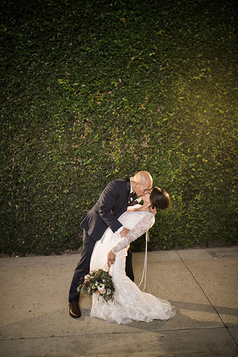 villa-del-sol-wedding-groom-dipping-bride-bride-in-a-lace-gown-with-long-sleeves-groom-in-a-navy-shawl-lapel-tuxedo-with-a-burgundy-tie
