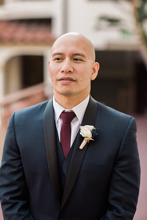 villa-del-sol-wedding-groom-in-a-navy-shawl-lapel-tuxedo-with-a-burgundy-tie