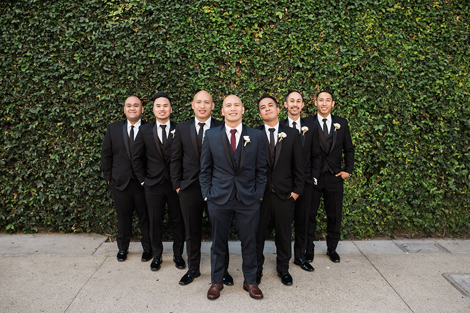 villa-del-sol-wedding-groomsmen-groom-in-a-navy-shawl-lapel-tuxedo-with-a-burgundy-tie-groomsmen-in-black-shawl-lapel-tuxedos