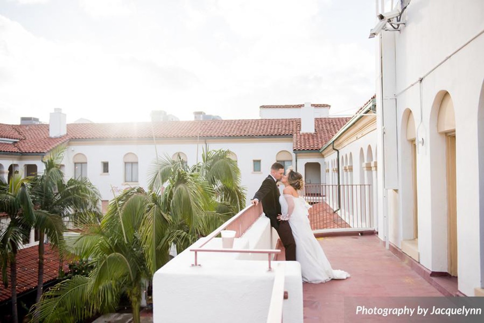 bride in a white silk gown with flowing sleeves and a high neckline and the groom in a black velvet tuxedo on balcony