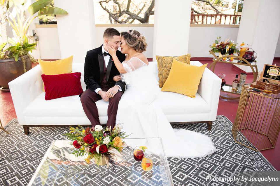 bride in a white silk gown with flowing sleeves and a high neckline and the groom in a black velvet tuxedo sitting on couch
