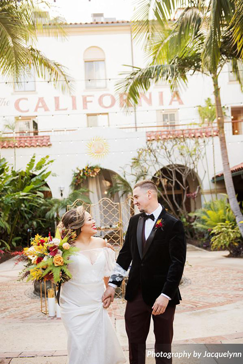 bride in a white silk gown with flowing sleeves and a high neckline and the groom in a black velvet tuxedo walking