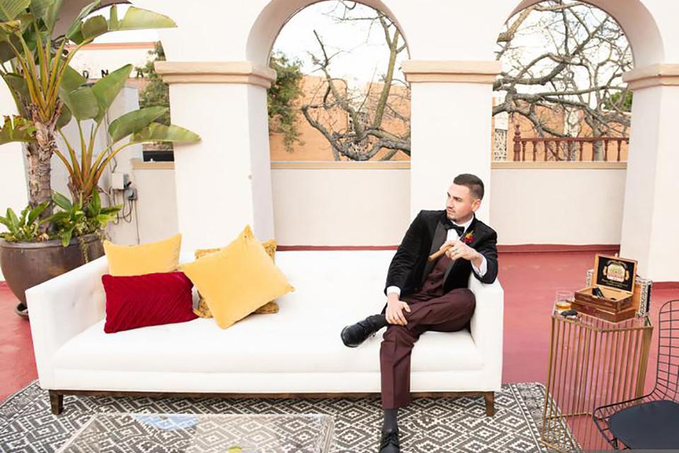 groom sitting on a couch in a black velvet tuxedo