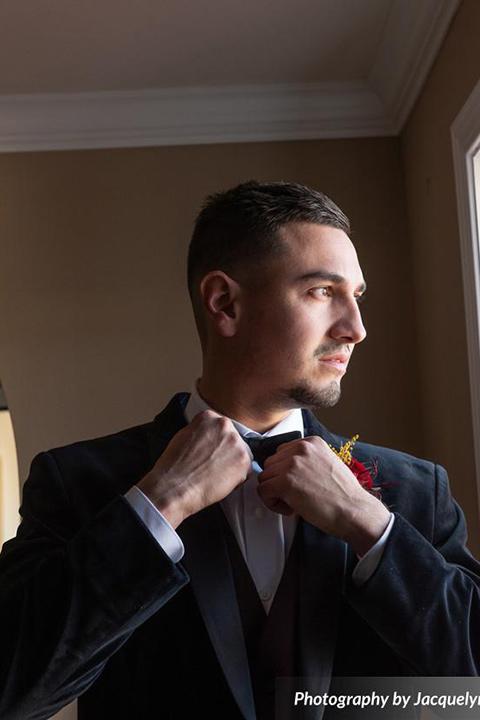 groom in a black velvet tuxedo with a black bow tie