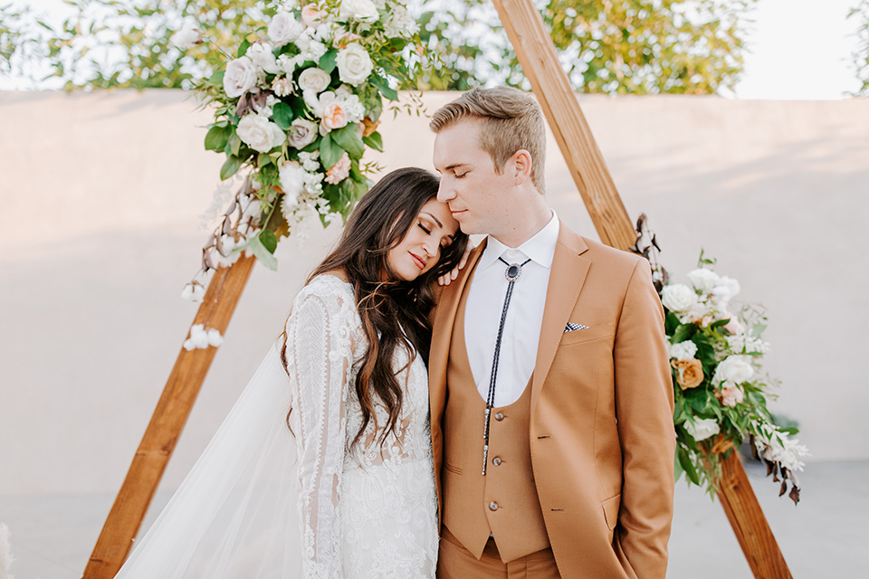 bride in a lace bohemian gown with long sleeves and the groom in a caramel suit with a bolo tie by geometric ceremony arch