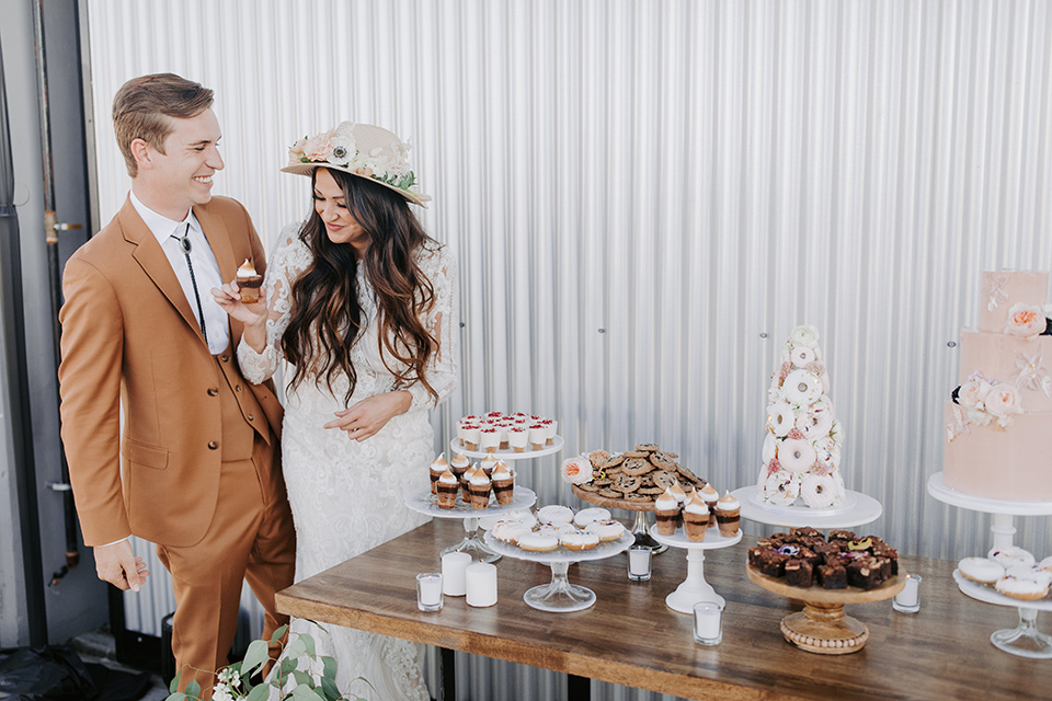 bride in a lace bohemian gown with long sleeves and the groom in a caramel suit with a bolo tie standing by dessert table