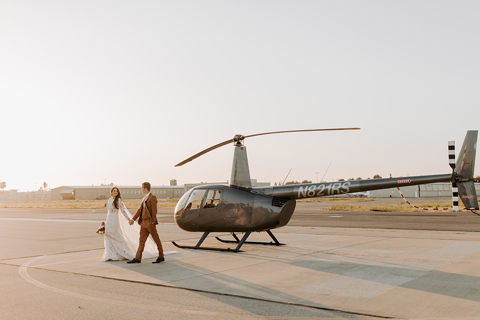bride in a lace bohemian gown with long sleeves and the groom in a caramel suit with a bolo tie by helicopter