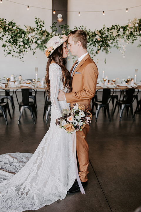 bride in a lace bohemian gown with long sleeves and the groom in a caramel suit with a bolo tie