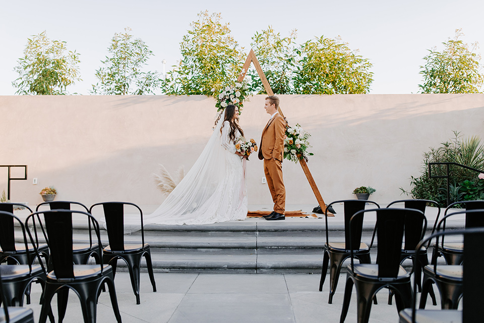 bride in a lace bohemian gown with long sleeves and the groom in a caramel suit with a bolo tie by table with a farmhouse bohemian style