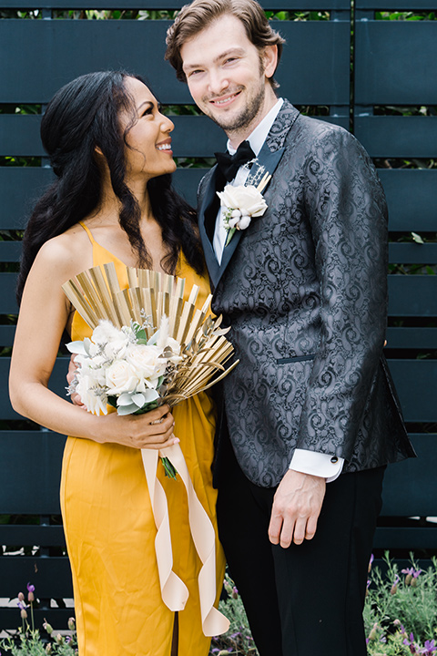 bridesmaid in a gold gown and groomsman in a black paisley tuxedo with a black bow tie