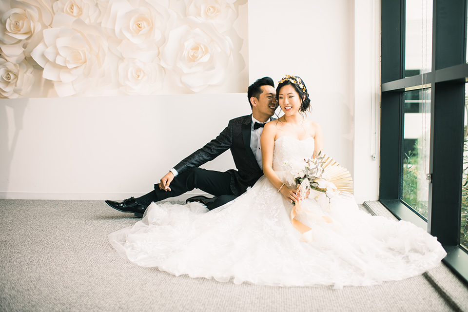 bride in a white gown with a strapless neckline and the groom in an ivory paisley tuxedo with a black bow tie both sitting by the window