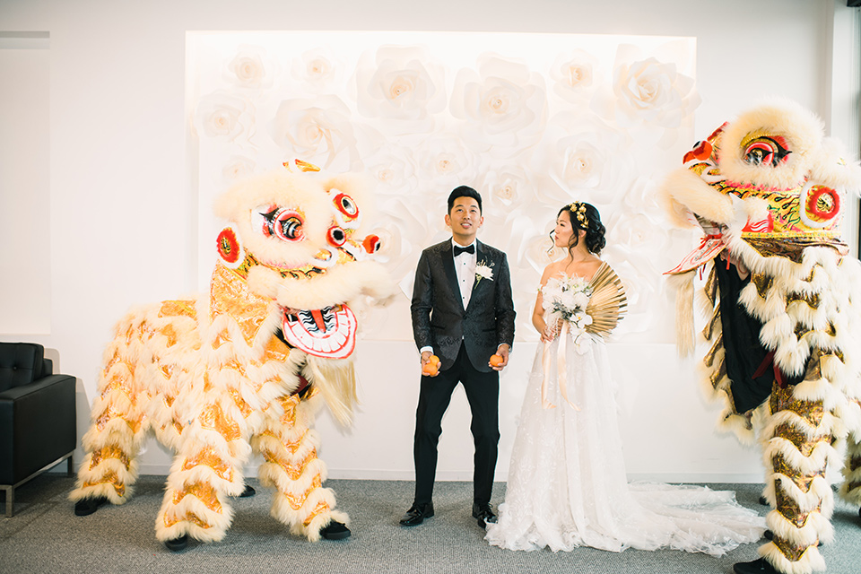 bride in a white gown with a strapless neckline and the groom in an ivory paisley tuxedo with a black bow tie with dragons outside