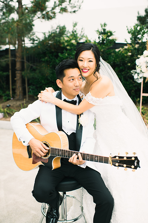 bride in a white gown with a strapless neckline and the groom in an ivory paisley tuxedo with a black bow tie with guitar