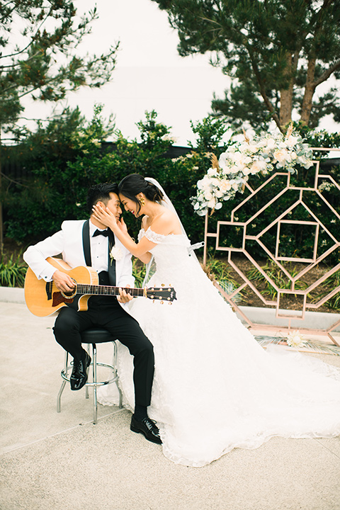 bride in a white gown with a strapless neckline and the groom in an ivory paisley tuxedo with a black bow tie with a guitar