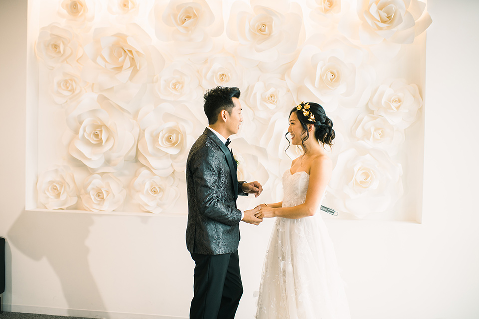 bride in a white gown with a strapless neckline and the groom in an ivory paisley tuxedo with a black bow tie at ceremony