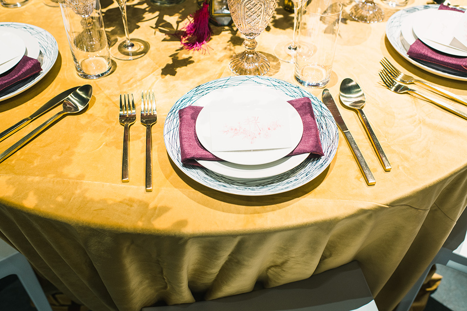 gold linens with burgundy napkins and gold flatware