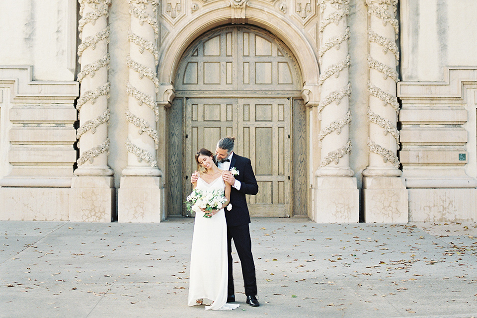 bride in a satin formfitting gown with thin straps, and the groom in a black notch lapel tuxedo with a black bow tie