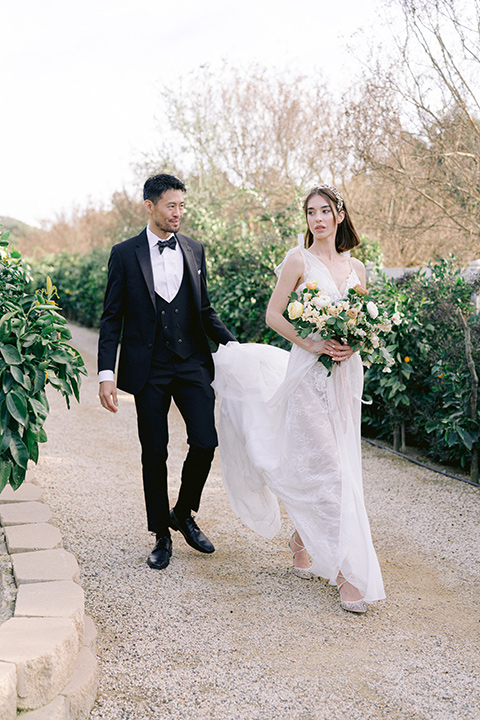 bride in a white lace gown with a flowing skirt with a high slit on the side, and tie straps.  The groom in a black michael kors tuxedo with a black bow tie