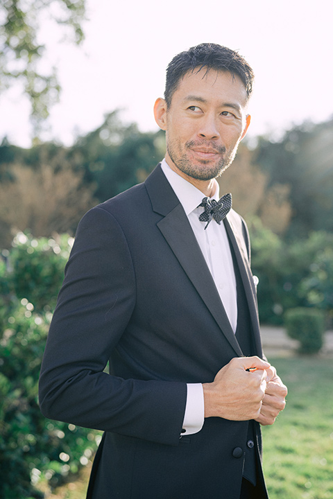 The groom in a black michael kors tuxedo with a black bow tie
