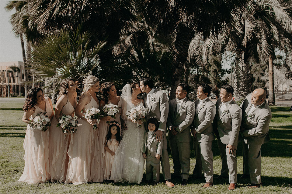 bride in a modern white gown with a v neckline and lace detailing, the groom in a light grey suit with a notch lapel and a white bow tie.  The groomsmen in light grey suits with blush bow ties and the bridesmaids in pink gowns
