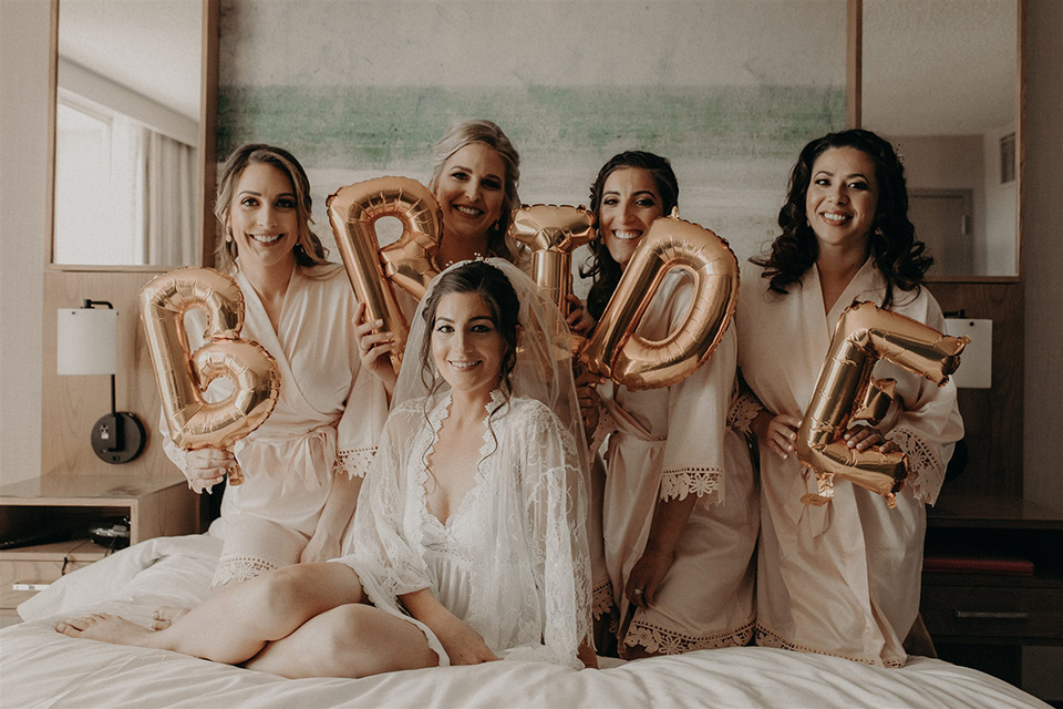bride and bridesmaids in robes with gold balloons