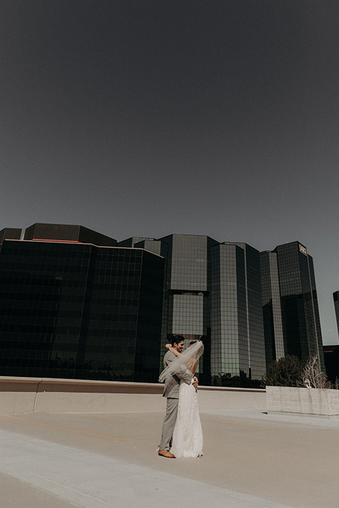 bride in a white lace gown with a v neckline and an elbow length veil and the groom in a light grey suit with a white long tie and brown shoes standing on the roof and kissing