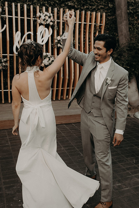 bride in a white lace gown with a v neckline and an elbow length veil and the groom in a light grey suit with a white long tie and brown shoes twirling