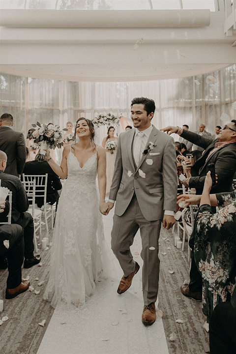 bride in a white lace gown with a v neckline and an elbow length veil and the groom in a light grey suit with a white long tie and brown shoes