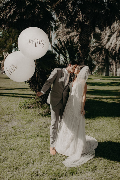bride in a white lace gown with a v neckline and an elbow length veil and the groom in a light grey suit with a white long tie and brown shoes holding big balloons