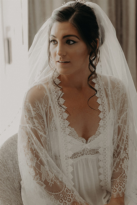 bride in a white lace robe getting her hair and makeup done