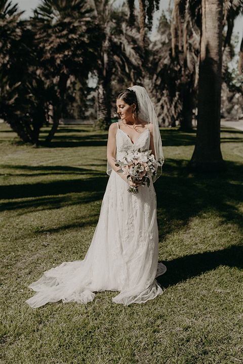 bride in a white lace gown with a v neckline and an elbow length veil
