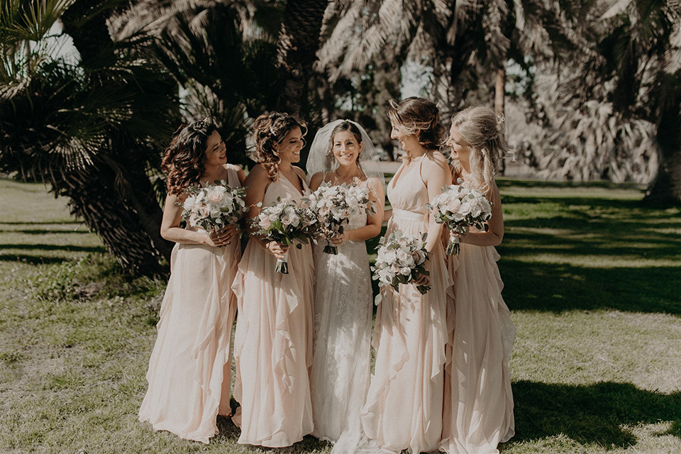 bride in a modern white gown with a v neckline and lace detailing and the bridesmaids in pink gowns