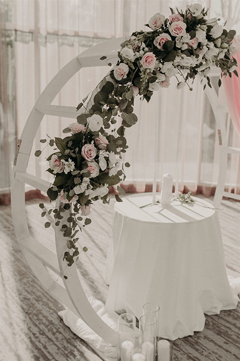 white ceremony arch with pink and green florals