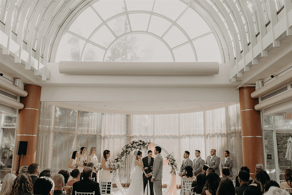 bride and groom at the ceremony with wide windows and arch
