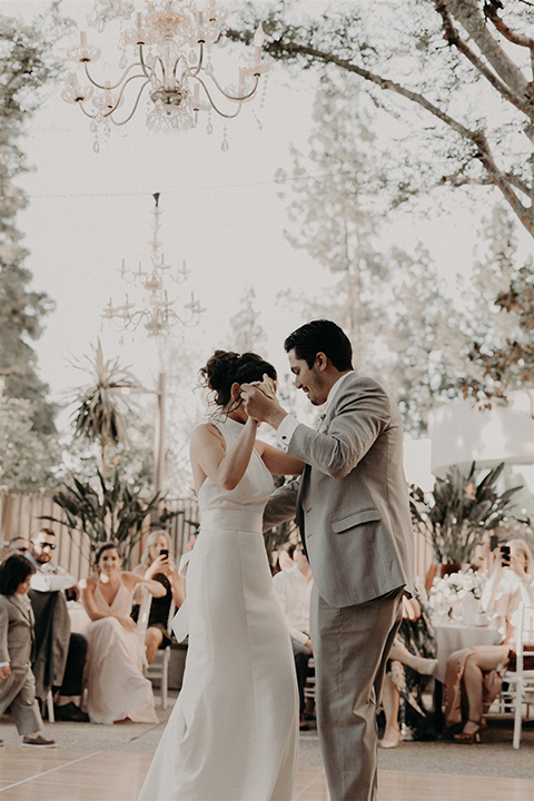 bride in a white modern gown with a high neckline and the groom in a light grey suit with a white long tie and brown shoes dancing