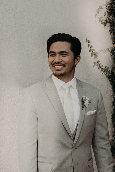 the groom in a light grey suit with a white long tie and brown shoes