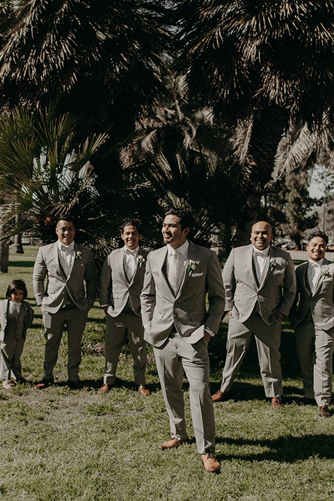 the groom in a light grey suit with a white long tie and brown shoes and groomsmen in light grey suits with pink bow ties