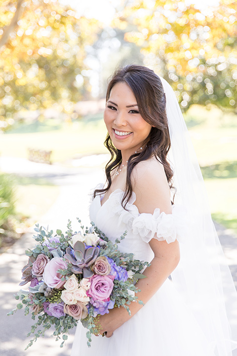 bride in a white a line gown with an off the shoulder neckline