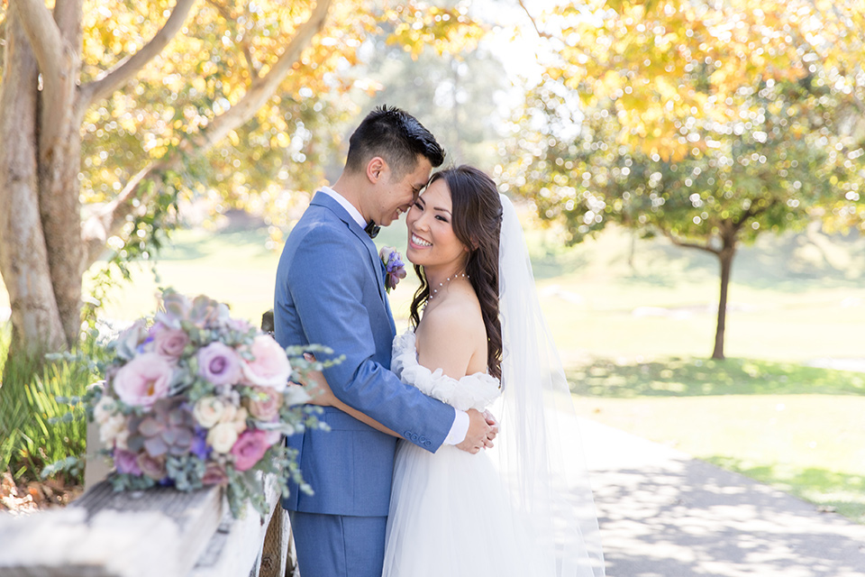 bride in a white gown with an off the shoulder neckline and the groom in a light blue suit with a blue bow tie