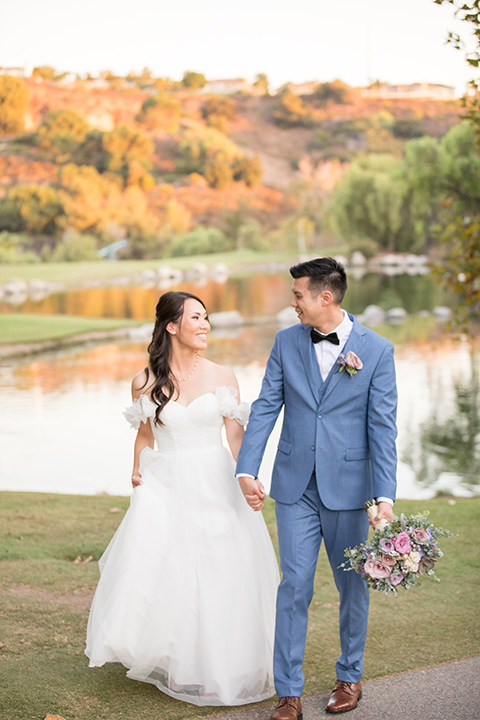 bride in a white gown with an off the shoulder neckline and the groom in a light blue suit with a blue bow tie, the groomsmen in light blue suits and the bridesmaids in lilac colored gowns