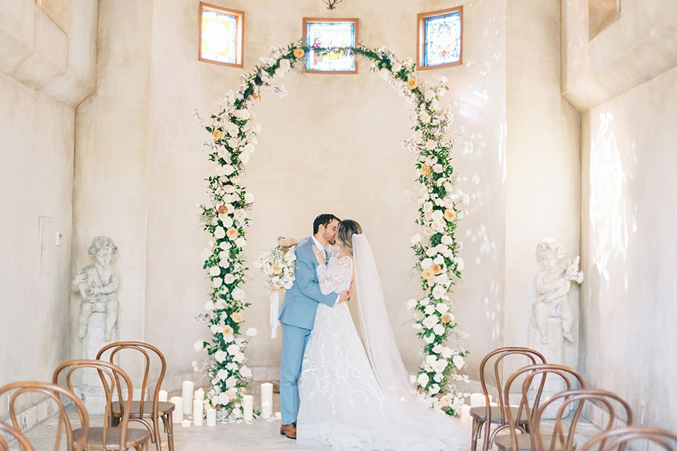 bride in a white ballgown with a low back detail and the groom in a light blue suit with a neutral long tie at the altar in chapel