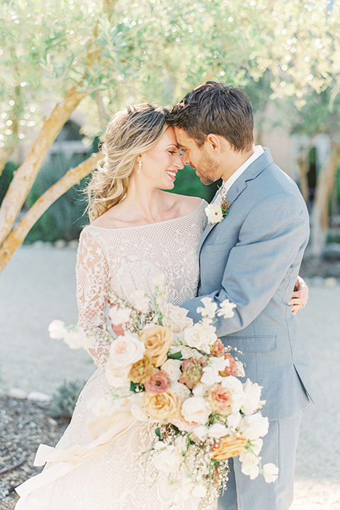 bride in a white ballgown with a low back detail and the groom in a light blue suit with a neutral long tie close together
